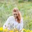 Smiling Redhead Woman Sitting Amid Flowers In Field — Stock Photo #26524231