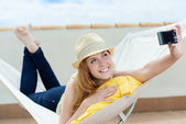 Smiling Woman Photographing Herself In Hammock — Stock Photo