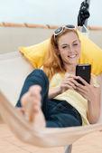 Mujer relajada con celular en hamaca — Foto de Stock