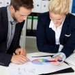 Smart Businessman And Woman Looking At Graphs — Stock Photo #26581155