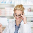 Pharmacist With Prescription Looking Over Glasses — Stock Photo #26586895