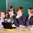 Schoolchildren looking at a laptop — Stock Photo