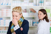 Young Blond Woman Coughing At The Pharmacy — Stock Photo