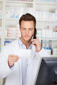 Pharmacist On Phone With Receipt At Drugstore — Stock Photo