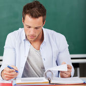 Thoughtful Man With Folder In Front Of Chalkboard — Stock Photo