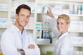 Two Smiling Pharmacists At Drugstore — Stock Photo