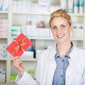 Young Female Pharmacist Holding Out Gift Coupon — Stock Photo