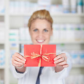 Female Pharmacist Holding Out Gift Coupon — Stock Photo