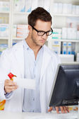 Pharmacist Checking Prescription At Drugstore — Stock Photo