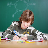 Young schoolboy writing notes — Stock Photo