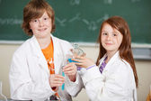 Young girl and boy doing chemistry — Stock Photo