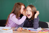 Two girls whispering in class — Stock Photo