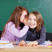 Happy little girls sharing a secret — Stock Photo