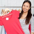 Smiling woman choosing a red shirt — Stock Photo