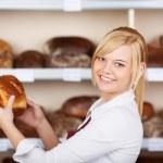 Saleswoman taking bread from shelf in bakery — Stock Photo