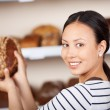 Stock Photo: Salewomholding wholemeal bread in bakery