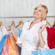 Woman With Shopping Bags Holding Blank Credit Card In Shop — Stock Photo