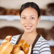Beautiful young woman working in bakery — Stock Photo