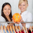 Women Holding Piggybank With Clothes Hanging On Rack At Shop — Stock Photo