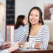 Smiling asian woman sitting in cafe — Stock Photo #26605619