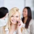 Smiling young woman using headset in the office — Stock Photo #26605625