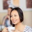 Smiling young woman in a cafe — Stock Photo #26605683
