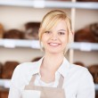 Saleswoman in bakery holding a cup of coffee — Stock Photo