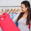 Young woman choosing shirt in shop — Stock Photo