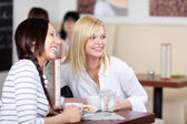 Smiling women watching someone in a cafe — Stock Photo