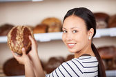 Salewoman holding wholemeal bread in bakery — Stock Photo