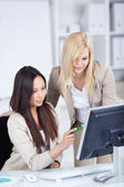 Female co worker working together on computer — Stock Photo