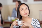 Daydreaming young woman drinking coffee — Stock Photo