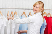 Confident young woman choosing shirt — Stock Photo