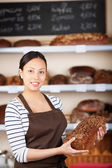 Salesgirl in bakery holding wholemeal bread — Stock Photo