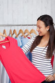 Young woman choosing shirt in shop — Stock Photo