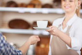 Girl in a coffeehouse serving a cup of coffee — Stock Photo