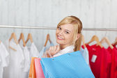 Young blond woman with bags looking back — Stock Photo