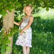 Beautiful little girl under a green tree — Stock Photo #26614095