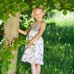 Beautiful little girl under a green tree — Stock Photo