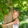 Stock Photo: Beautiful young girl hugging tree