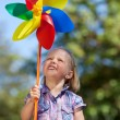 Cute little girl watching colourful pinwheel — Stock Photo #26614435