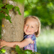 Happy little girl hugging a tree — Stock Photo