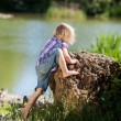 Stock Photo: Little girl clambering onto rock