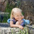 Stock Photo: Little girl enjoys warm rock
