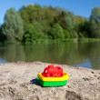 Little colourful plastic boat at the lake — Stock Photo