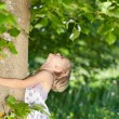 Young girl hugging a tree trunk — Stock Photo