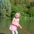 Pretty little girl fishing at the lake — Stock Photo
