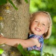Stock Photo: Beautiful little blond girl hugging tree