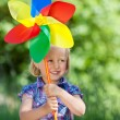 Cute young girl with a colourful windmill — Stock Photo #26616199