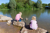 Two small girls feeding ducks on a lake — Stock Photo